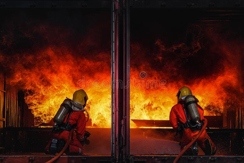 Firefighters training Team practice to fighting with fire in emergency situation. Spray water to the flame in closed location stock photography