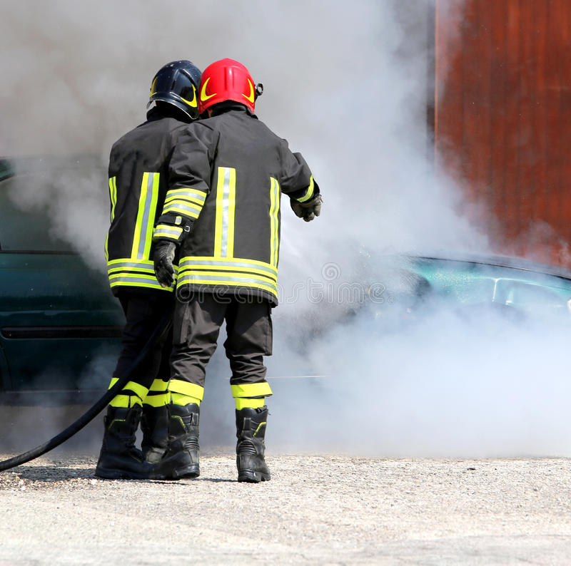 Firefighters with uniform and protective helmet extinguish. Two firefighters with uniform and protective helmet extinguish the fire of the incident car during a stock photos