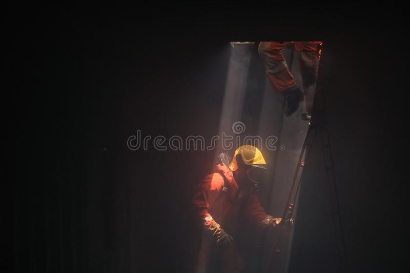 Firefighters went to rescue the fire from  chimney above. Firefighters went to rescue the fire from the chimney above stock photo