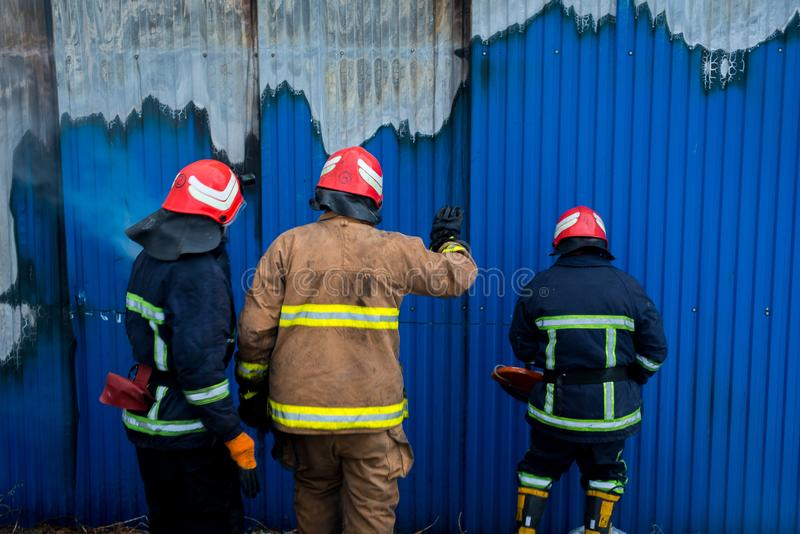 Firefighters work on an fire of building using a metal cutter rescue tool during a fire. fire extinguish stock photo