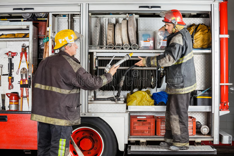 Firefighters Working At Truck In Fire Station. Mature and young firefighters working at truck in fire station stock photos