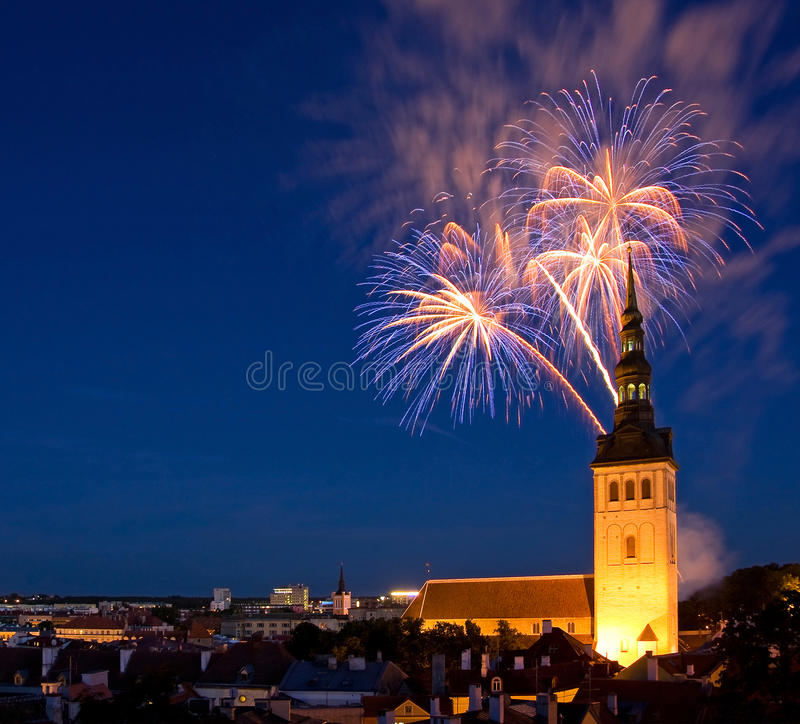 Fireworks in Tallinn, Estonia. A photo of a fireworks in the Old Town of Tallinn, the capital of Estonia, Europe. In front of fireworks there is a church Saint stock photo