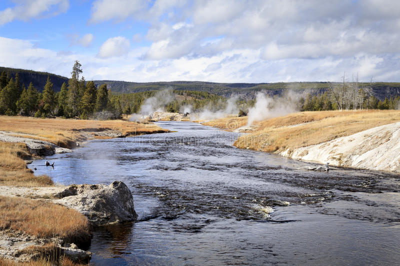 Firehole River. You can see how Firehole River got its name. Multiple geothermal vents, springs, and geysers line its banks, pumping out steam and spilling stock photography