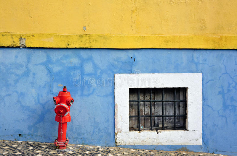 Firehydrant and window. A fire hydrant, also called fireplug, is a connection point by which firefighters can tap into a water supply. It is a component of royalty free stock image