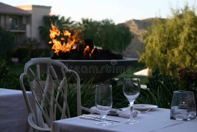 Firelit dinner at sunset stock image