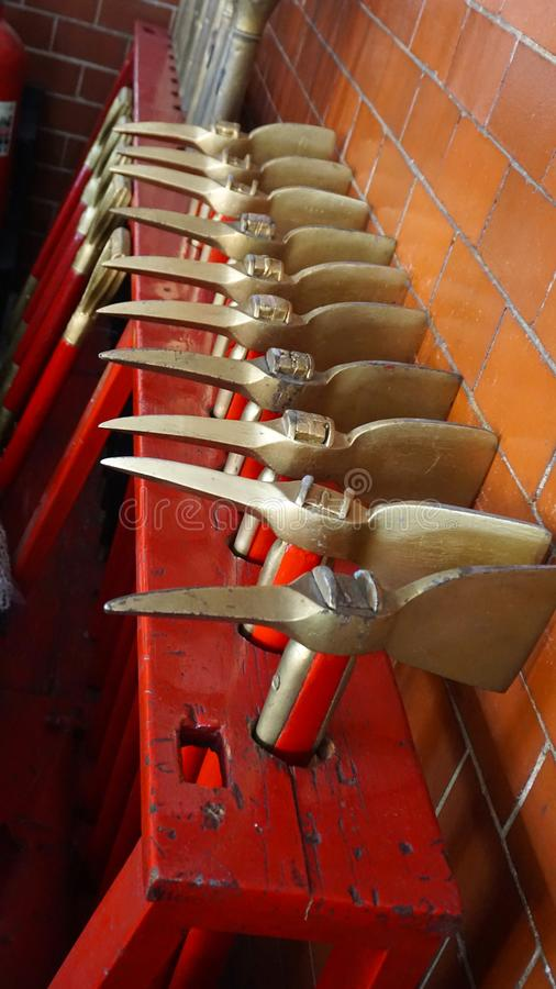 Fireman axes. Many axes painted in gold and red, stacked together in a fire station in mexico, tools used by fireman to break doors and other debris stock images