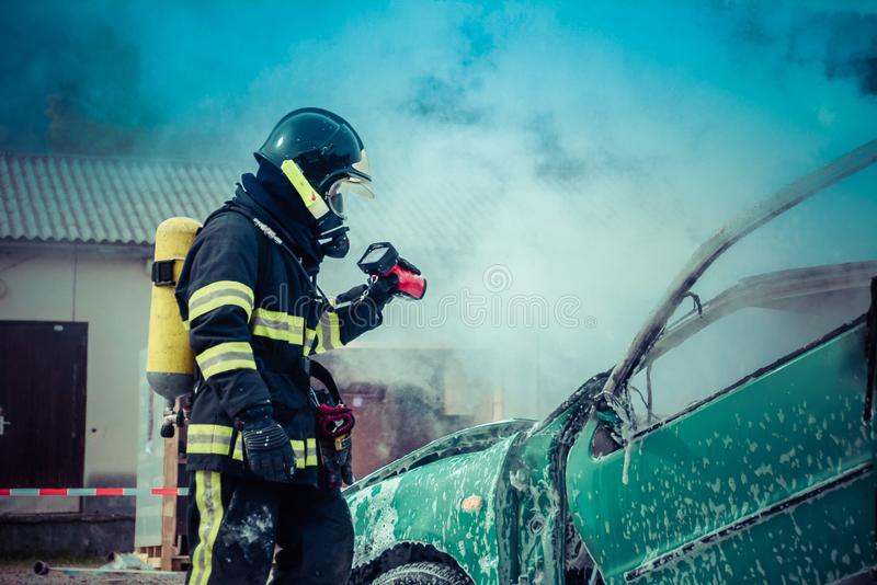 Fireman checking hot spot with thermal camera. Fireman is checking hot spot with thermal camera on a burned vehicle stock image