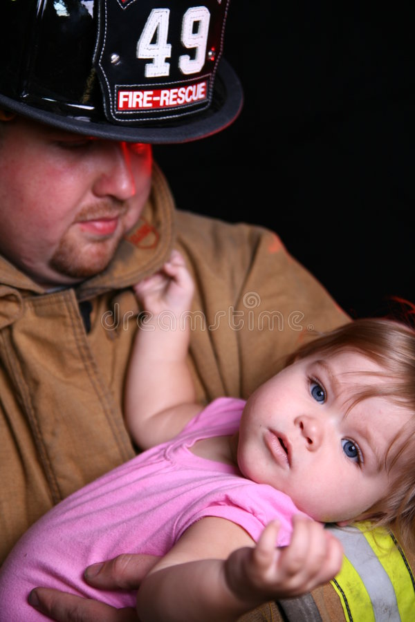 Fireman and Child. Fireman holds baby girl in his arms royalty free stock photos