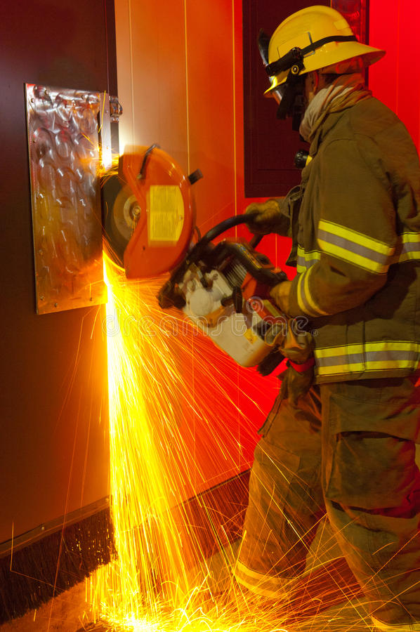 Fireman cutting through door. With sparks & slight motion blur royalty free stock photo