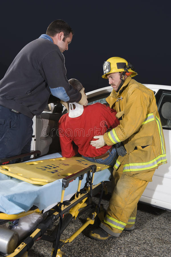 Fireman And Doctor Taking Out Victim From Car royalty free stock image
