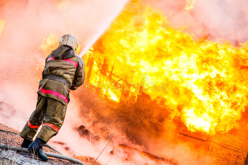 Fireman extinguishes a fire. In an old wooden house stock photo