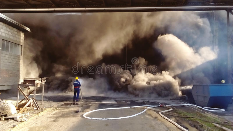 Fireman in front of a big fire fire extinguishing stock image