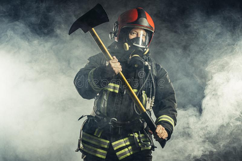 Fireman with hammer don`t afraid of danger and fire. Caucasian fireman hero, ready to protect all humanity from fire, professional firefighter in protective stock images