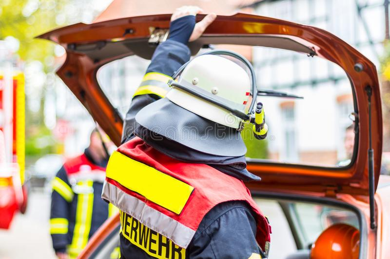 Fireman with helmet holds his hand on car bootlid royalty free stock images