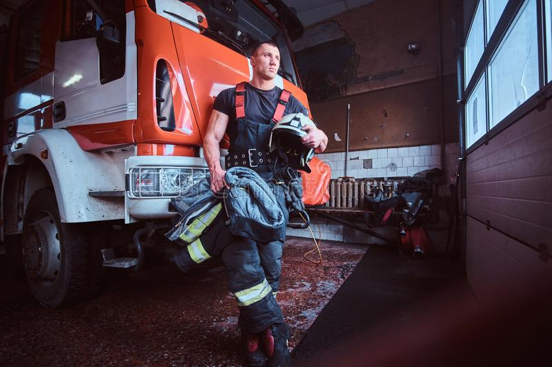 Young fireman holding a jacket and protective helmet in a garage of a fire department, leaning on a fire engine and royalty free stock image