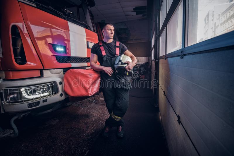 Young fireman holding a jacket and protective helmet in a garage of a fire department, leaning on a fire engine and royalty free stock photo