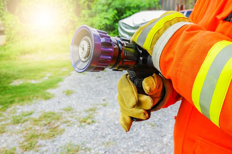 Fireman holds and adjust nozzle and fire hose spraying high pressure water royalty free stock photo