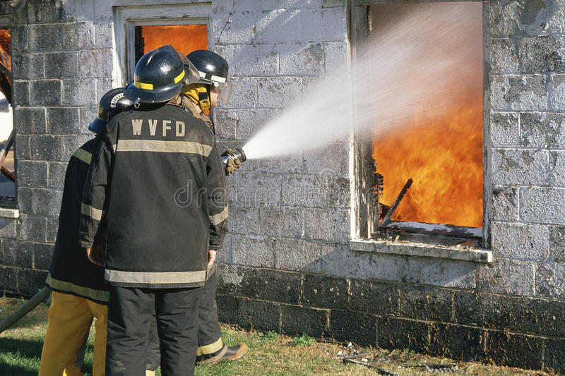 Fireman hosing down a burning building royalty free stock photo