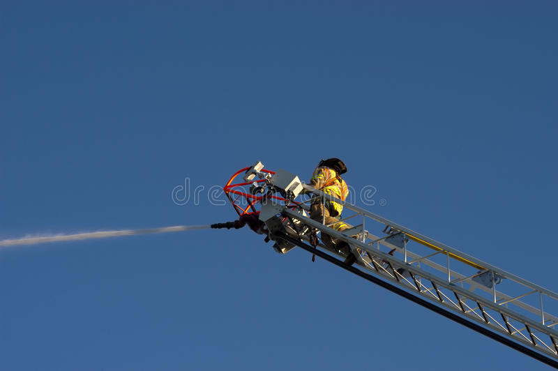 Fireman on Ladder Truck Spray Water on Fire. A fireman at work fighting a fire from a ladder truck and spraying water on a fire with the hose. Many consider stock photos