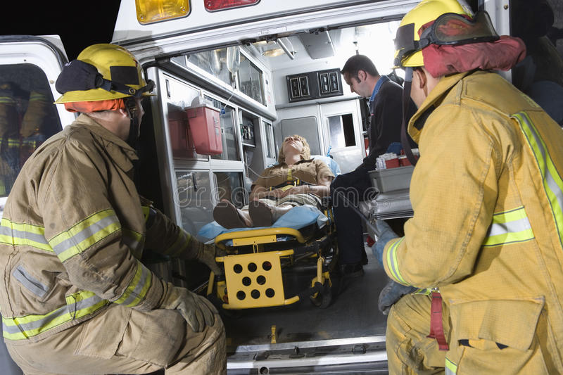 Fireman Looking At Patient And EMT Doctor. Fire workers looking at patient and EMT doctor in the ambulance royalty free stock photos
