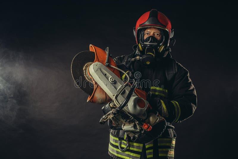 Fireman med motorsåg isolerat över rökig bakgrund royaltyfri foto