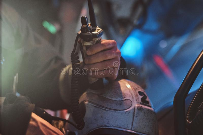 Fireman in a protective uniform sitting in the fire truck and holding walkie-talkie. Hand close up. The fire brigade arrived at the night-time royalty free stock images