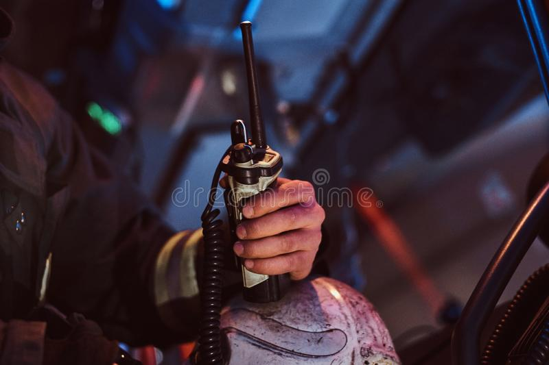 Fireman in a protective uniform sitting in the fire truck and holding walkie-talkie. Hand close up. The fire brigade arrived at the night-time royalty free stock image