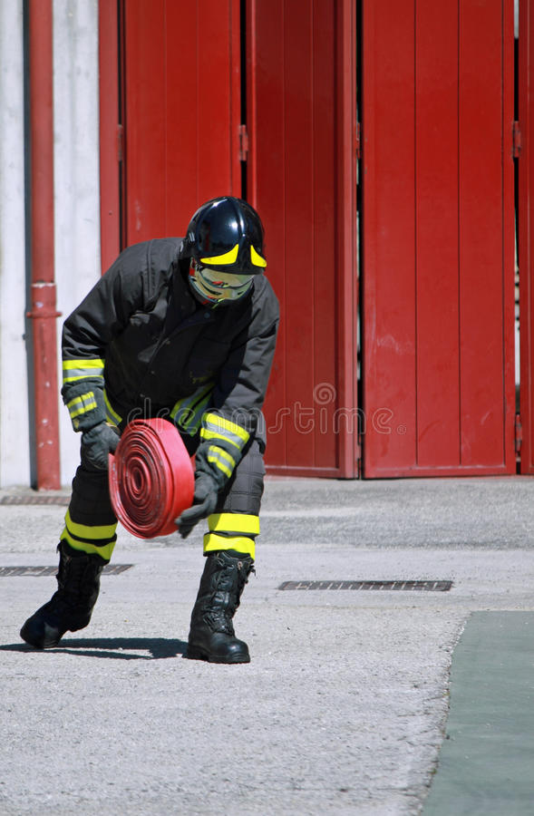 Fireman while unrolls a fire hose. Italian Fireman while unrolls a fire hose to extinguish the flames royalty free stock image