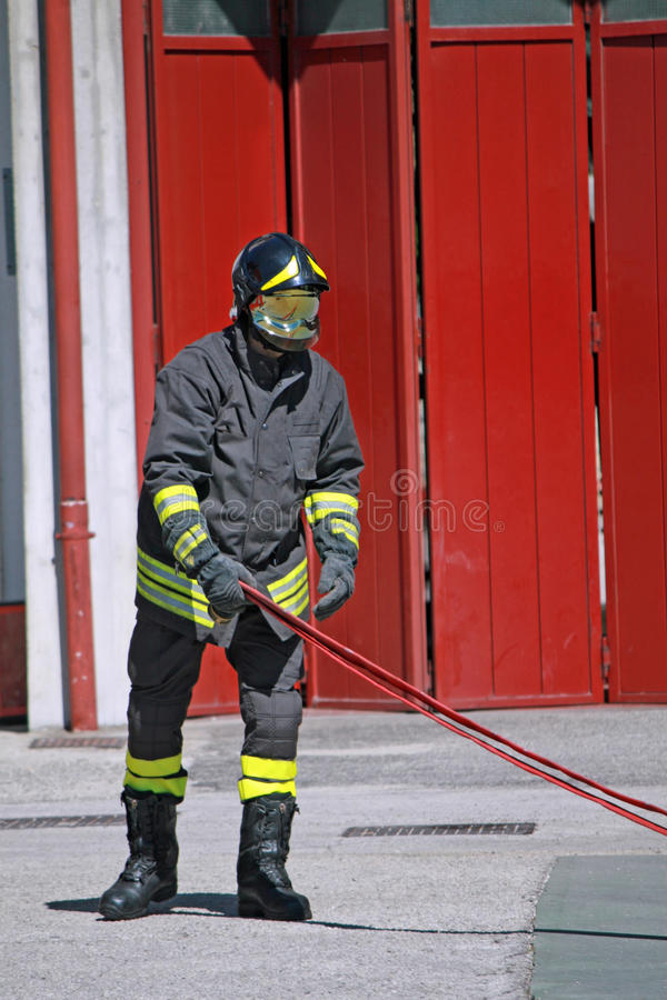 Fireman while unrolls a fire hose to extinguish the flames. Italian Fireman while unrolls a fire hose to extinguish the flames stock photo