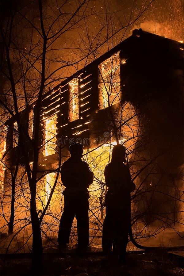 Firemans, das zum sicheren Haus auf Feuer versucht Feuerwehrmann Emergency Ext stockfotografie