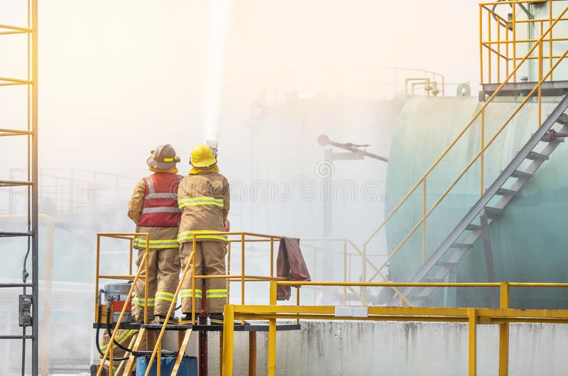 Firemans in yellow fire fighter uniform holding fire hose nozzle spraying foam water control fighting. In the industrial factory during basic fire fighting royalty free stock images