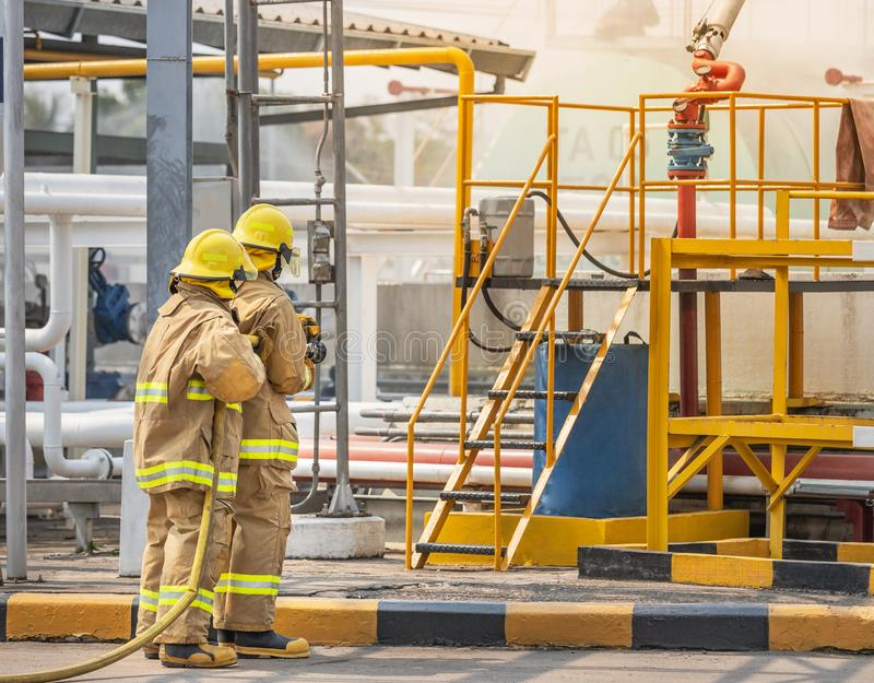 Firemans in yellow fire fighter uniform holding fire hose nozzle spraying foam water control fighting. In the industrial factory during basic fire fighting stock images