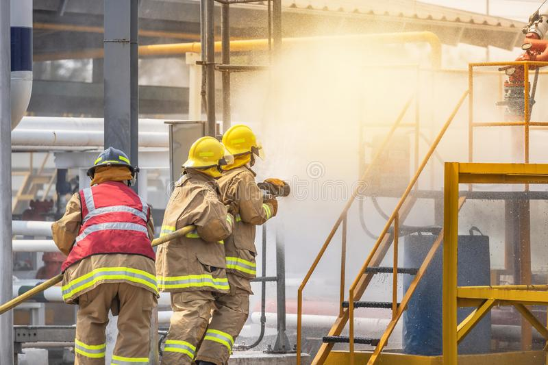 Firemans in yellow fire fighter uniform holding fire hose nozzle spraying foam water control fighting. In the industrial factory during basic fire fighting royalty free stock photo