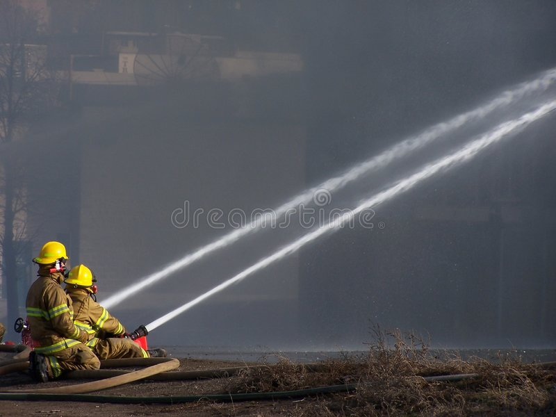 Firemen. Two firemen fighting a fire