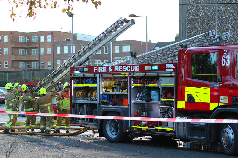 Firemen attending a fire. Firemen removing ladders to get to a fire at a block of flats in Bedford, UK on Friday 23rd November, 2012. A fire had broken out in stock images