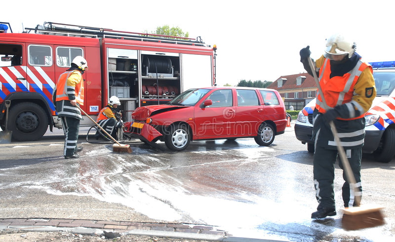 Firemen cleaning. The street after a car-crash stock image