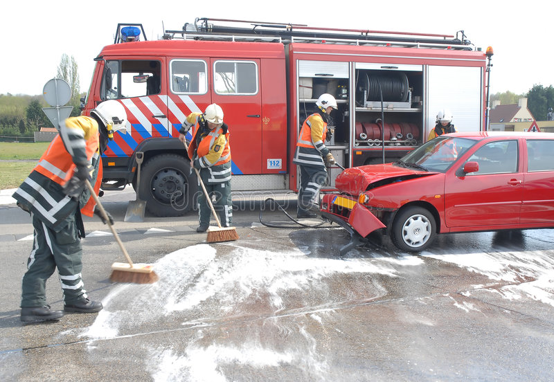 Firemen cleaning up. Firemen cleaning the street after a car-crash stock photos