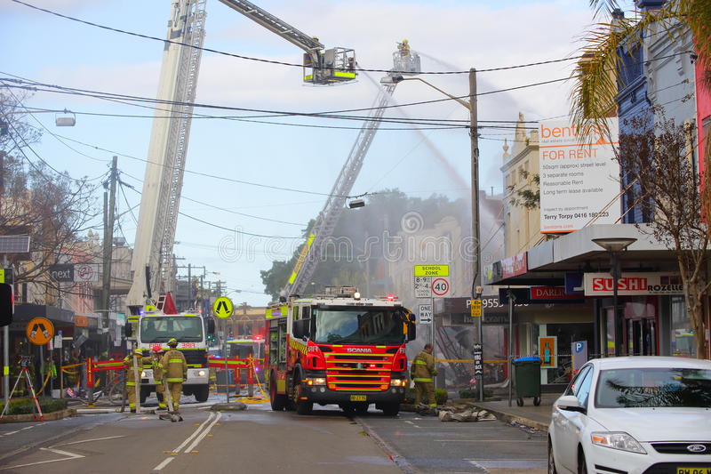 Firemen douse flames after explosion at a convenience store in R. ROZELLE, AUSTRALIA - SEPTEMBER 4, 2014; Firefighters on cranes douse the flames of a royalty free stock image