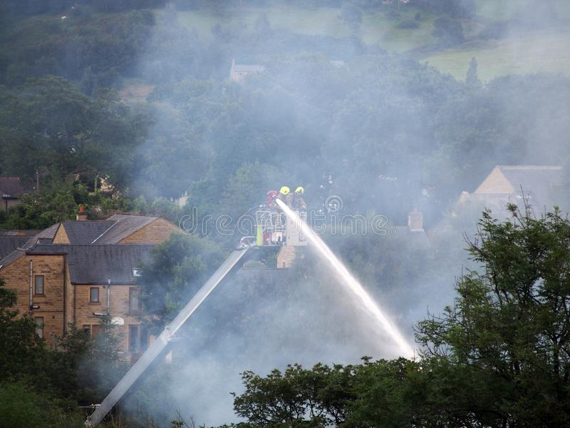 Firemen on an elevated platform putting out the fire at the former walkeys clogs mill in hebden bridge stock photos