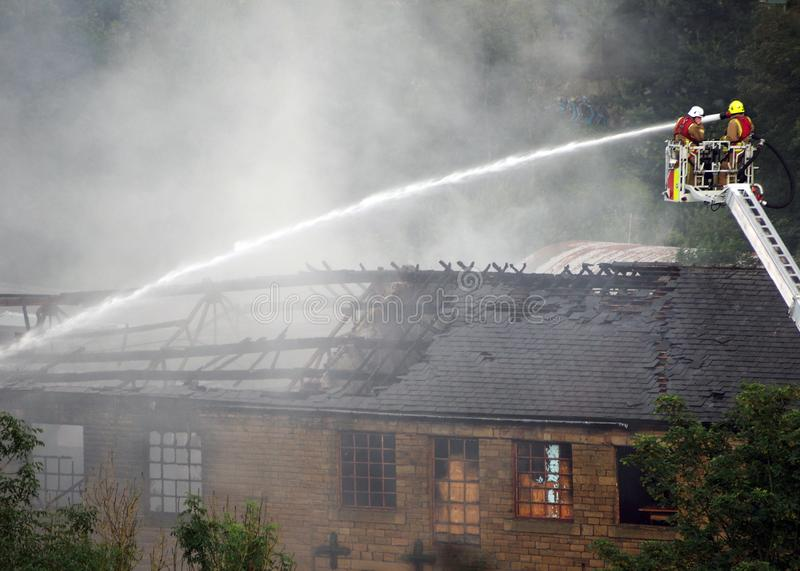 Firemen on an elevated platform putting out the fire at the former walkeys clogs mill in hebden bridge royalty free stock photo
