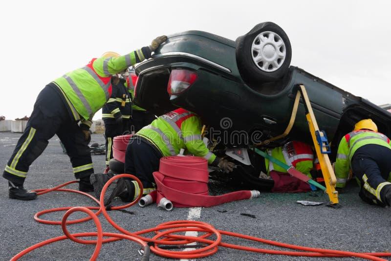 Firemen with equipment at car crash