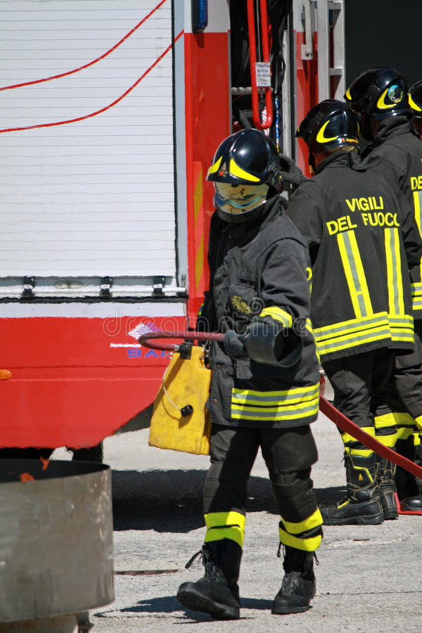 Firemen extinguish a simulated fire. Italian Firemen extinguish a simulated fire during an exercise in their Firehouse royalty free stock photography