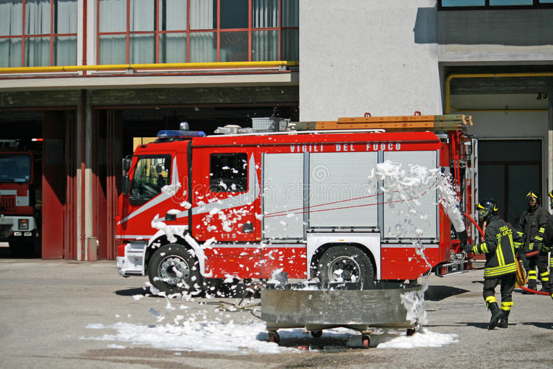 Firemen extinguish a simulated fire during an exercise in their. Italian Firemen extinguish a simulated fire during an exercise in their Firehouse royalty free stock photography