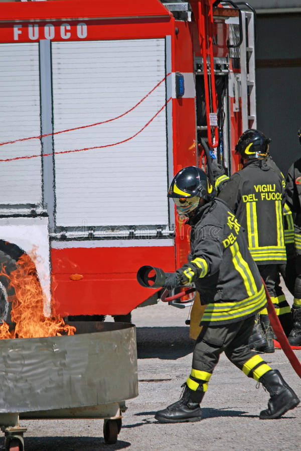 Firemen extinguish a simulated fire during an exercise in their. Italian Firemen extinguish a simulated fire during an exercise in their Firehouse royalty free stock photo