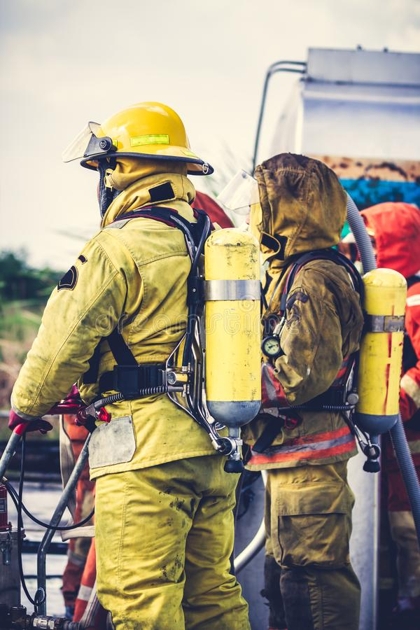 Firemen in firefighter uniform preparing equipment and tool. Firemen in firefighter suits with foam extinguisher preparing equipment and tool for action. During stock photos