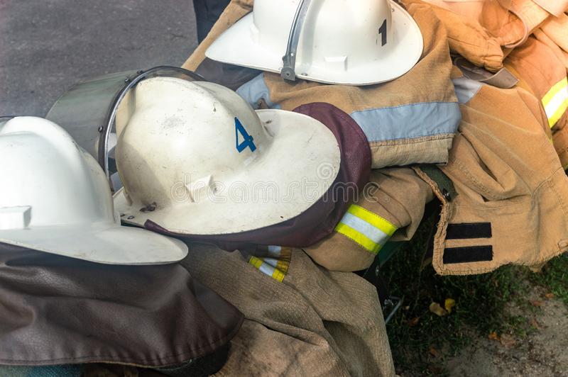 Firemen`s helmets clothing firefighters on the street royalty free stock images