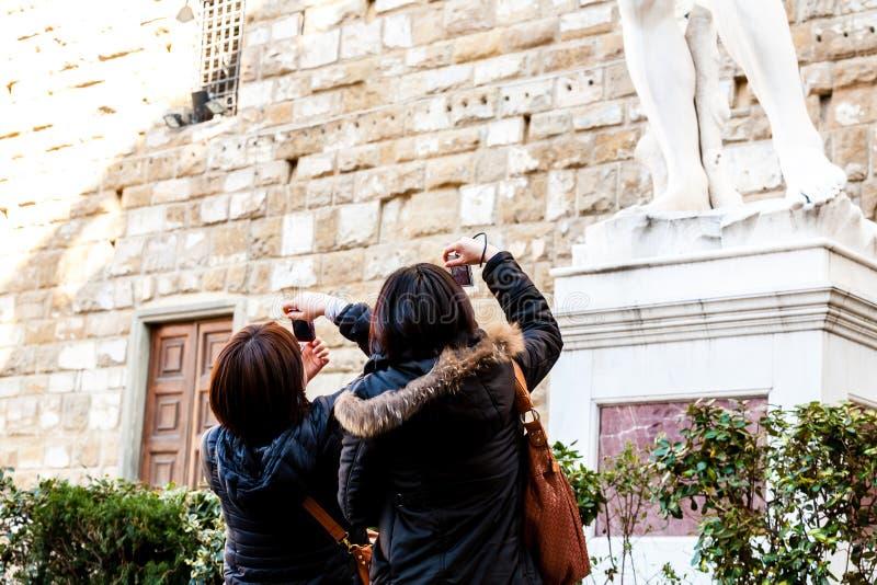 Firenze, Italia - 13 marzo 2012: Giovani turisti che prendono le immagini della statua vicino alle gallerie di Uffizi fotografie stock libere da diritti