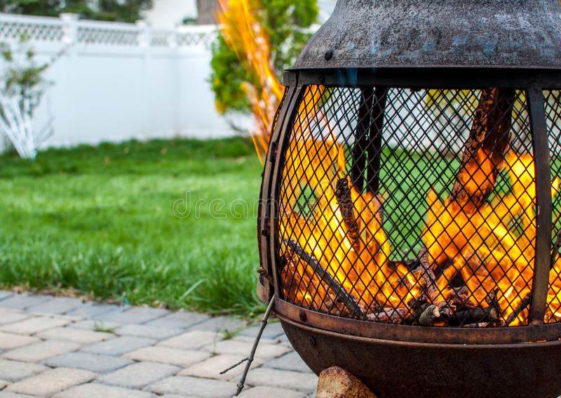 Firepit en patio trasero con el fuego del rugido fotografía de archivo libre de regalías