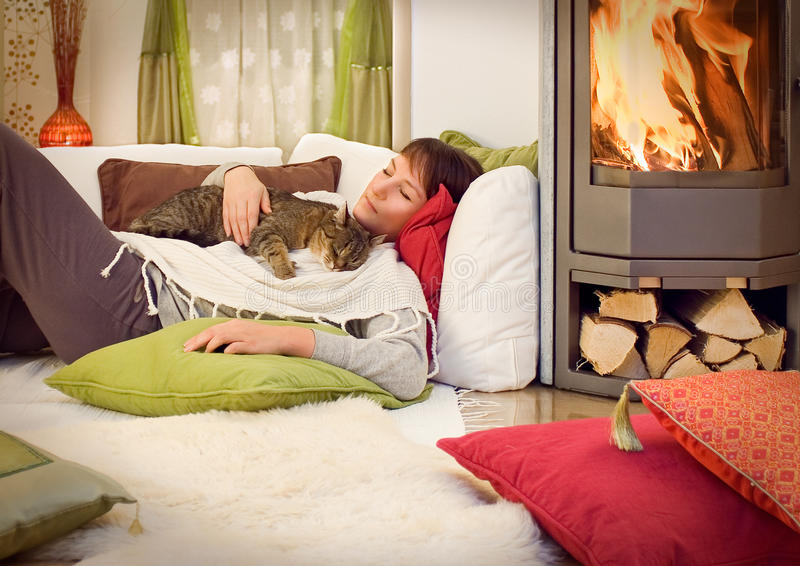 Fireplace 3. Woman is lying at a fireplace with a cat