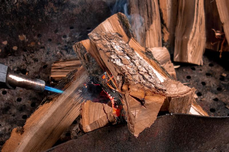 Fireplace kindling of chopped wood logs by gas torch. Method of firing at camping outdoor. Close up image of burning woods and stock photos
